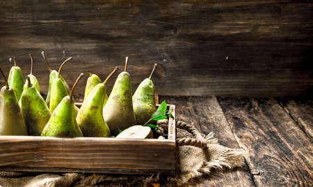Fresh pears on an old tray. On a wooden background.