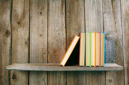 Books on a wooden shelf. On a wooden background.