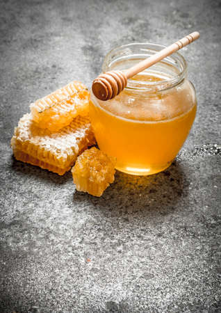 Fresh honey in jar with wooden spoon. On rustic background.