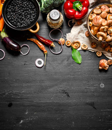 Organic food. Fresh vegetables with mushrooms and black beans. On a black chalkboard.