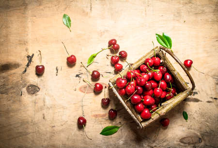 basket of red cherry and leaves . On a wooden table. Standard-Bild