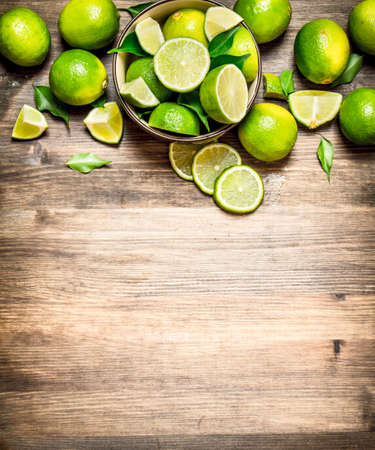 Ripe limes in a bowl. On a wooden table.
