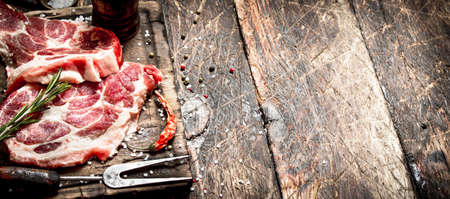Raw meat background. Pieces of raw steak with spices and herbs. On wooden background.