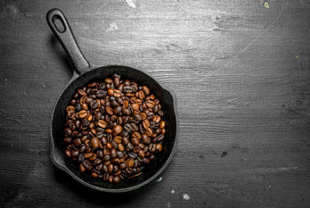 Fried coffee beans in a frying pan. On the black chalkboard.