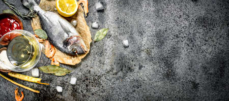 Unprocessed Dorado fish with spices and lemon. On a rustic background. Standard-Bild