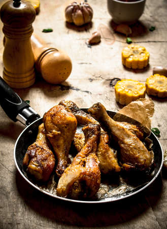 Fried chicken legs with corn and garlic. On a wooden table.