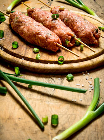 Raw kebab with green onions on the Board. On a wooden table.