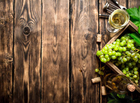 White wine with a box full of grapes. On a wooden table. Standard-Bild