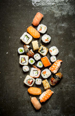 Different sushi and rolls with seafood. On the stone table.