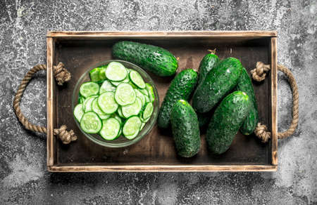 Fresh cucumbers in an old tray. on a rustic background. Standard-Bild