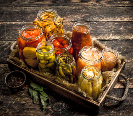 Preserves food with vegetables and mushrooms on an old tray. On a wooden background. Standard-Bild