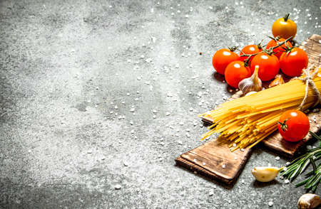 Pasta background. Spaghetti with garlic and tomatoes. On rustic background.