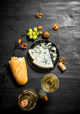 White wine with French blue cheese and nuts. On black wooden board