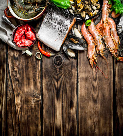 Fresh seafood. A variety of seafood from shrimp, shellfish and other marine life. On wooden background.
