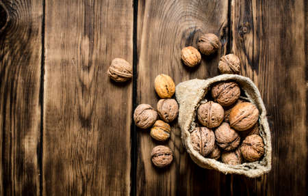 Walnuts in the old bag. On a wooden table.