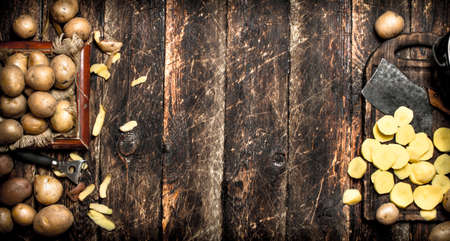The sliced potatoes on an old wooden Board. On wooden background. Standard-Bild