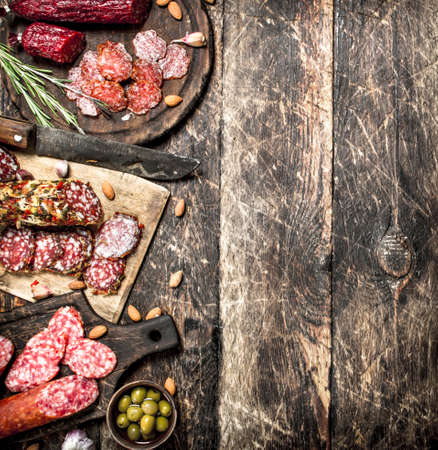 Different kinds of salami on the boards. On a wooden background.