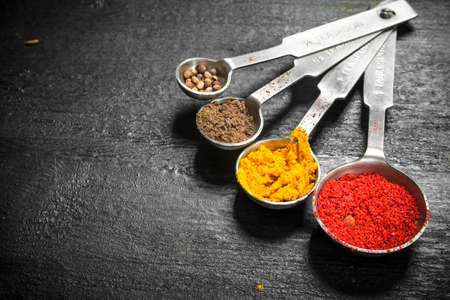 Ground spices in measuring spoons. On the black chalkboard.
