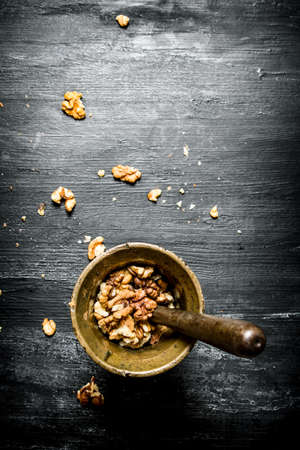 Shelled walnuts in a mortar with pestle. On black rustic table.