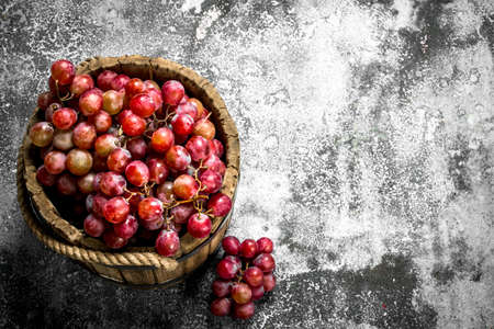 Fresh red grapes in a wooden bucket. On a rustic background.