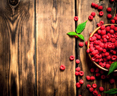 Wild raspberry with leaves in a bowl. On a wooden table. Standard-Bild