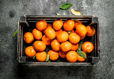 Fresh mandarins in an old box. On a rustic background.