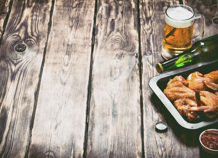 Smoked chicken wings with beer and sauce. On a wooden table.