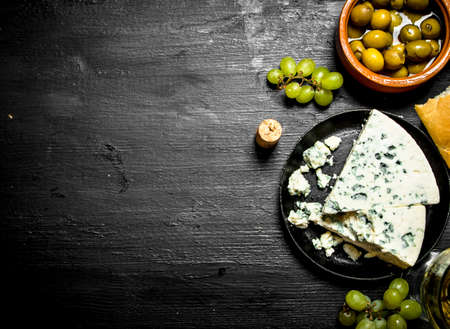 Blue cheese, olives and white grapes. On a black wooden background.