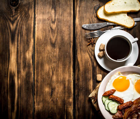 fresh Breakfast. Cup of coffee , fried bacon with eggs and smoked sausage. On wooden background. Standard-Bild