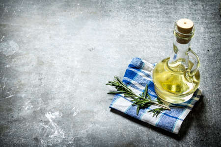 Olive oil with rosemary branch. On a stone background.