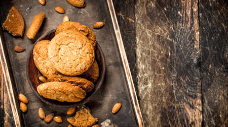 Oatmeal cookies with nuts. On a wooden background.