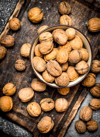Walnuts in a bowl. On rustic background.