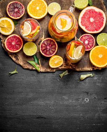 Citrus background. Fresh citrus juice with slices of limes, oranges, grapefruits and lemons. On black chalkboard. Standard-Bild