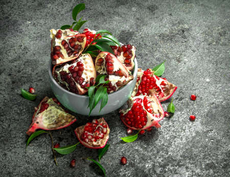 Ripe pieces of pomegranate in a bowl. On a rustic background.