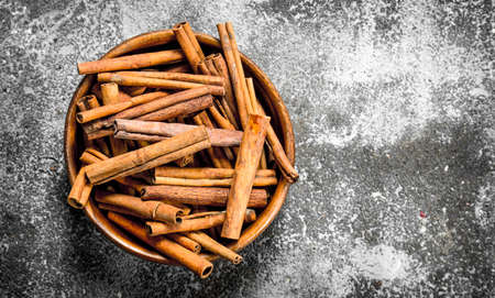 Sticks of cinnamon in a bowl. On rustic background .