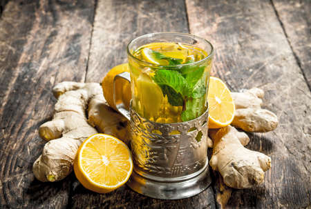 Ginger tea with mint and lemon. On wooden background. Standard-Bild