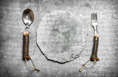 Empty stone plate with spoon and fork. On a stone background. Standard-Bild