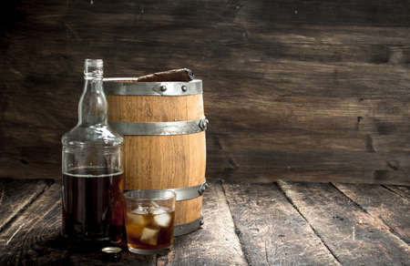 Whiskey background. A barrel of Scotch whiskey with glass and a cigar. On a wooden background. Reklamní fotografie