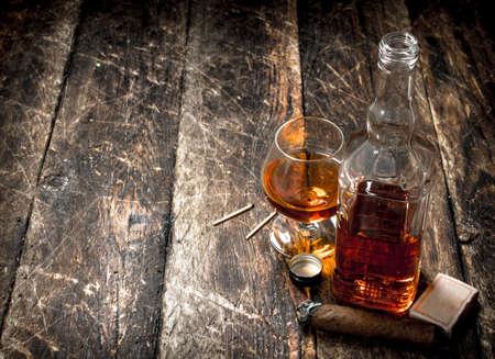 French cognac with a cigar. On a wooden background.