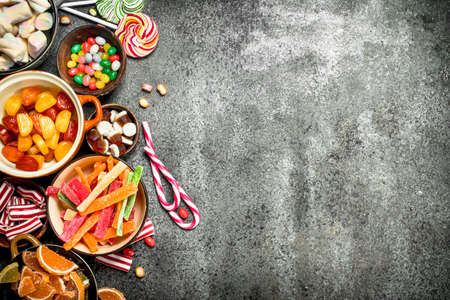 Multicolored candy, jelly and marshmallows in a bowl. On a rustic background.