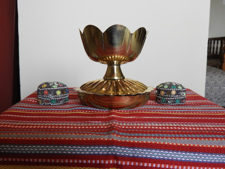 bronze bowl on red mat with traditional kumkum holders decoration