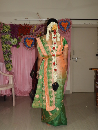 hindu bride showing her back with long hair decorated with rose flowers, jasmine flowers