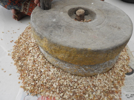 grinding cow peas with millstone in Indian house