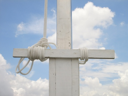 tight focus: A white flag pole base with a white rope tied off