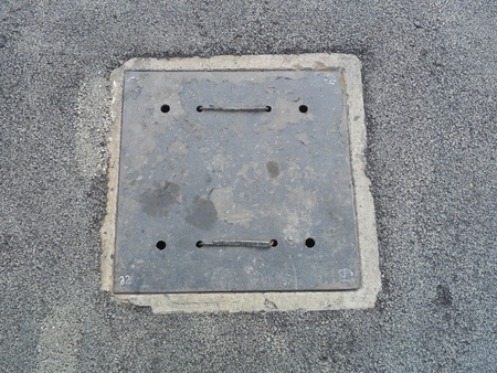 Square metal sewer hatch with light rust on the concrete surface