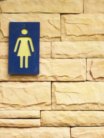 bathroom sign: Ladies bathroom sign on a brick wall