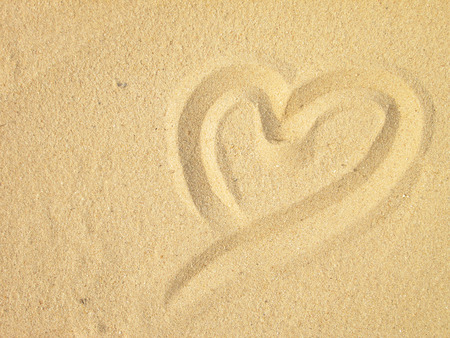 evoking: Heart drawn on sand. Horizontal composition