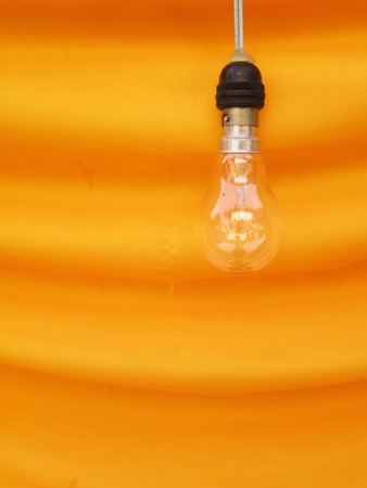 t bulb: Lamp on the orange fabric Stock Photo