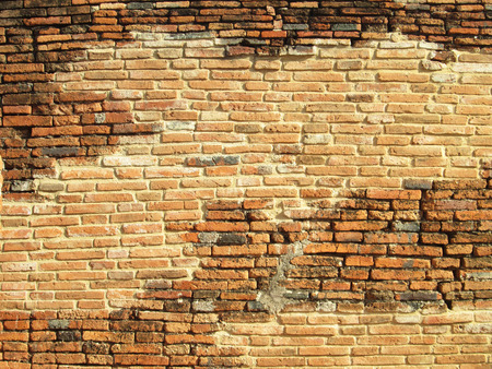 very old brick wall brick faces damaged with time background texture photo