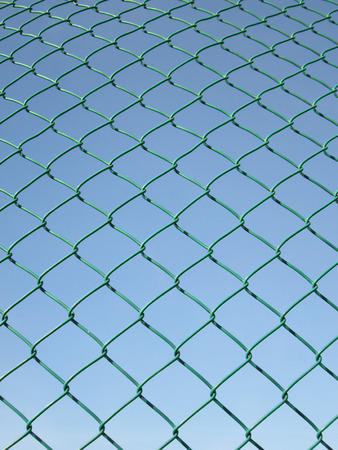 Green seamless fence chain, Iron wire fence on blue sky background photo